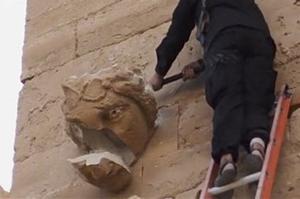 Un Djihadiste tapant à coups de masse sur un bas-relief de la cité antique d'Hatra