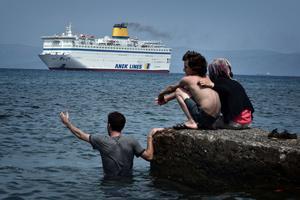 Des migrants syriens regardent arriver à Kos le ferry prévu pour servir d'hôtel temporaire de 2500 places, vendredi.