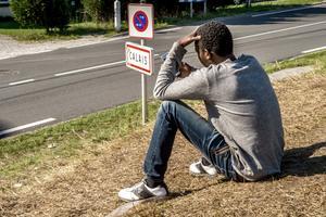 Un migrant patientant à Calais, été 2015.
