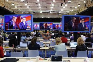 Les journalistes regardent le débat sur écrans géants.