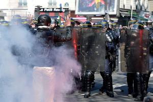 Un manifestant fait face aux forces de l'ordre, dimanche à Paris, sous des nuages de gaz lacrymogène.