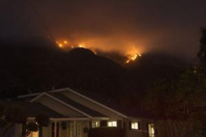 Derrière les habitations, les flammes consument les forêts. (AFP)