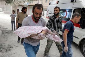 Un homme porte le corps d'un enfant retrouvé sous les décombres d'un immeuble bombardé.