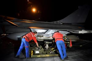 Des techniciens installent un missile sur un Rafale, la veille de l'intervention.