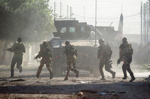 En colonne derrière un véhicule blindé, des soldats des forces spéciales irakiennes tentent de poursuivre leur avancée dans Mossoul malgré la résistance des combattants de l'État islamique.