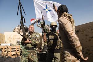 Des combattants de la milice chrétienne NPU, ici à Qaraqosh. Les unités de protection de la plaine de la Ninive, portent sur le haut du bras droit un écusson en forme d'étoile bleue à quatre branches avec au centre un cercle d'or représentant le dieu soleil assyrien Shamash.
