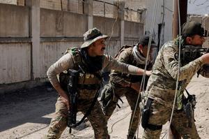 Un sniper de la Force de réaction rapide, une unité spéciale de la police irakienne, sécurise, le 9 mars, l'avancée de ses camarades de combat dans l'ouest de Mossoul.