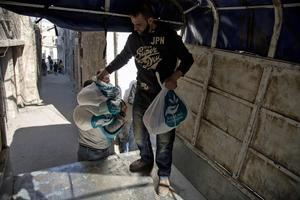 Une famille syrienne reçoit des vivres près d'Alep, mardi.