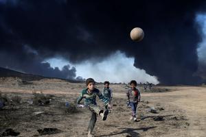 Un garçon joue au football près d'un puits de pétrole incendié par l'EI, au sud de Mossoul.