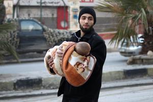 Un père et son enfant fuient les combats à Alep-est.