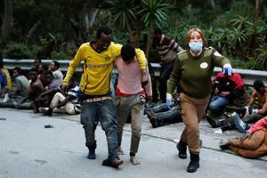 Des migrants s'entraident alors qu'ils approchent du centre de rétention.