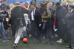Emmanuel Macron jouant au football avec des jeunes
