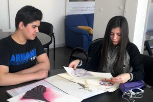 Nadeen expose ses dessins à Khaldoun, un bénéficiaire du réseau Nawaya.