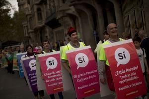 Des manifestants portent des bannières scandant «oui», samedi, lors d'une manifestation à Barcelone, à laquelle ont participé les maires favorables au scrutin.