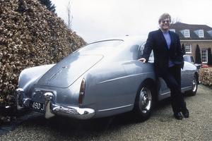 Sir Elton John devant sa Bentley.