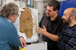 Pascal Godefroit, Paul Tafforeau et Andrea Cau examinent le fossile d'Halszkaraptor.
