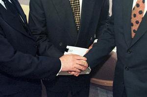 Poignée de mains historique entre le premier ministre britannique Tony Blair, son homologue irlandais Bertie Ahern, et le sénateur américain George Mitchell , le 10 avril 1998.