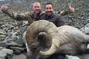 Luc Alphand à côté d'un mouflon.