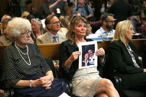 Au tribunal, une femme montre une photo d'un couple tué en 1981.
