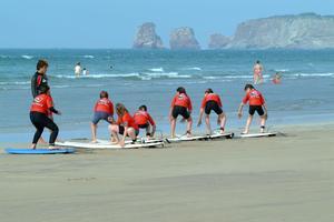 Cours de surf sur la plage d'Hendaye, vue sur les Deux Jumeaux