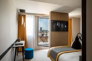 L'une des 134 chambres au mobilier épuré en bois blond et tabouret au tissu bleu saphir lumineux.