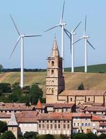 Près de Toulouse, à Avignonet-Lauragais, une ferme éolienne surplombe, domine et trouble la quiétude de ce village occitan séculaire. L'église Notre-Dame-des-Miracles, avec son clocher octogonal flanqué d'une tourelle d'escalier, n'a pas pu résister à l'envahisseur.