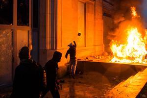 Un homme jette une pierre devant le Musée de l'Orangerie à côté d'un véhicule en flammes samedi 1er décembre.