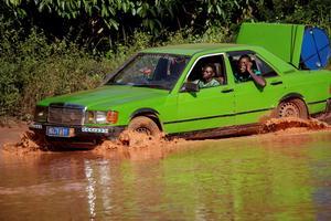 Sur la route du cacao, un taxi s'enfonce jusqu'à mi-roues dans un trou d'eau.