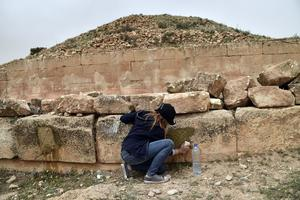 Les étudiants en archéologie nettoient, à la brosse et à l'eau, les symboles gravés sur certaines pierres.