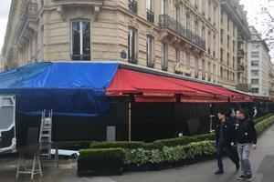 En partie brûlé, le store du Fouquet's arbore une grande bâche bleue.
