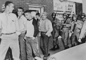 La 101e division aéroportée pousse une foule de jeunes hommes blancs à partir de devant le lycée central à Little Rock dans l'Arkansas. en septembre-octobre 1957.