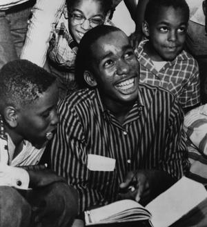 Ernest Green, un des neuf lycéens noirs de Little Rock, montre son nouveau manuel à ses amis, après son premier jour complet au lycée central de Little Rock en septembre 1957.