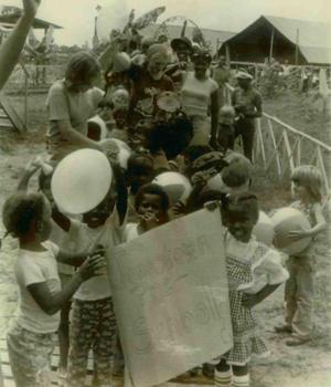 Des enfants de l'école maternelle de Jonestown lors d'un défilé portant une affiche.