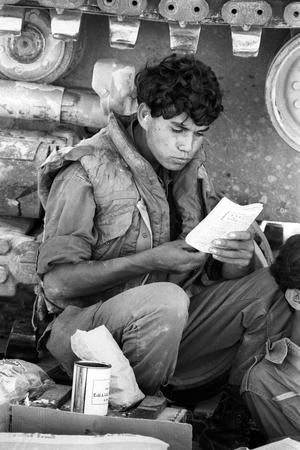 Un jeune israélien lisant un cahier sur le front syrien (plateau du Golan) lors de la guerre du Kippour en octobre 1973.