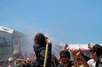 Un membre du staff arrosant les festivaliers touchés par la chaleur
