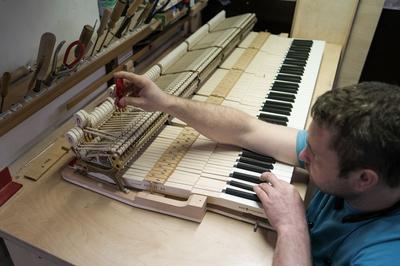 Un ouvrier fixe les marteaux d'un des mille pianos produits par l'entreprise chaque année.