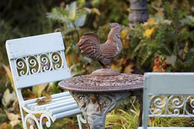 Chaises et bancs en métal ouvragé des années 1930 parsèment le jardin.