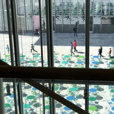 Tout en verre et béton, le centre culturel de la fondation Stavros Niarchos propose à son entrée une agora aux tables multicolores pour se retrouver.
