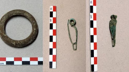 Bracelet en lignite (à gauche) et fibules de bronze.