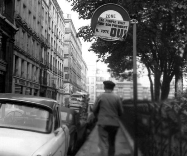 Un homme passe devant une affiche appelant à voter «oui» au référendum sur l'élection présidentielle au suffrage direct, collée sur un panneau de signalisation, le 18 octobre 1962 à Paris.