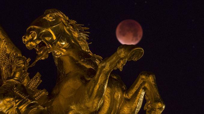 A Paris, la lune est apparue dans une couleur rouge sombre. Ici, la photo a été prise à côté d'une des statues du pont Alexandre III, ce lundi