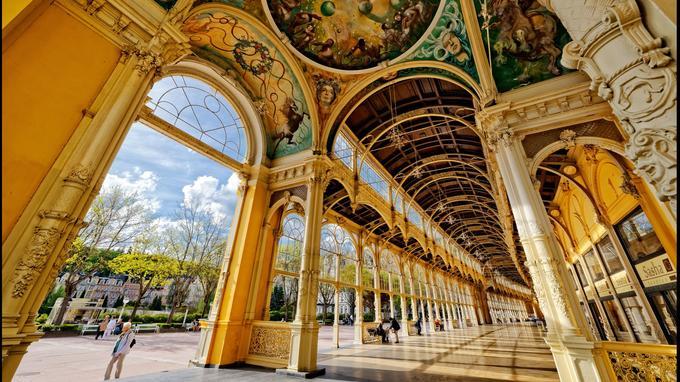 La Kolonada , construite en 1889, est l'édifice iconique de Marienbad. Les arcades et les pylônes sont typiques de la période Eiffel. En revanche, la fresque est contemporaine: elle date de 1981 et a été réalisée par Josef Vylet'al.