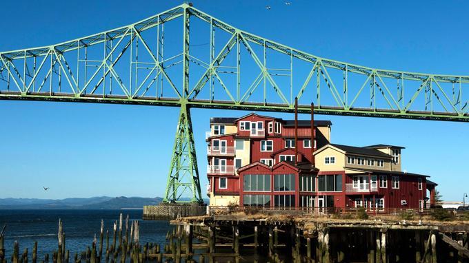 A l'embouchure du fleuve Columbia, le pont d'Astoria marque la limite septentrionale de l'Etat d'Oregon. A ses pieds, une ancienne conserverie de poissons reconvertie en hôtel.