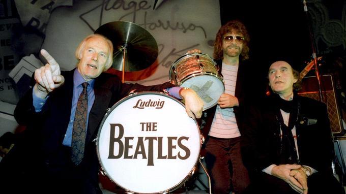 George Martin répond lors d'une conférence de presse, en 1965, aux côtés de Jeff Lyne, producteur du single Free as Bird, et Neil Aspinall, manager des beatles devenu directeur de leur compagnie Apple Corps.