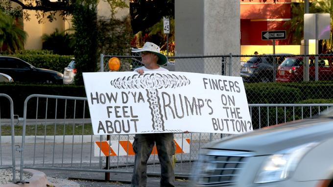 Un homme s'inquiète de la potentielle politique étrangère de Donald Trump, devant le Bank United Center de l'université de Miami, avant le début du débat républicain.