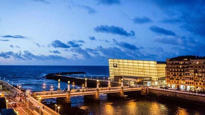 La nuit tombe sur l'embouchure du fleuve Urumea. Chef-d'œuvre Art déco, le pont de Zurriola tranche avec le bâtiment futuriste qui annonce la capitale culturelle de l'Europe en 2016.
