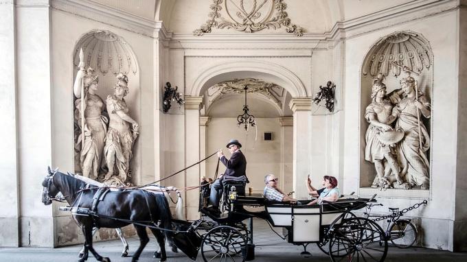 Un fiacre traversant la Hofburg, immense palais qui est une ville dans la ville. Vienne possède près de 150 fiacres, dont les conducteurs portent une tenue traditionnelle. Ces voitures et leurs chevaux font partie du paysage viennois