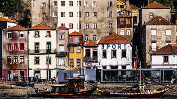 Atmosphère festive et populaire. Une terrasse dans un cube de verre côtoie les vieilles maisons des quais du Douro.