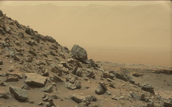 Derrière la pente recouverte de débris rocheux, on aperçoit au loin, dans un fond d'atmosphère poussiéreuse, les bords du cratère de Gale.