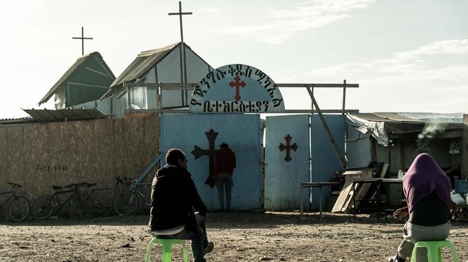 Assis devant l'église et la mosquée, des migrants assistent au démantèlement du cvamp.